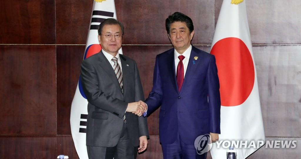 资料图片:2019年12月24日,在成都香格里拉酒店,韩国总统文在寅(左)和日本首相安倍晋三在会谈开始前握手合影。 韩联社