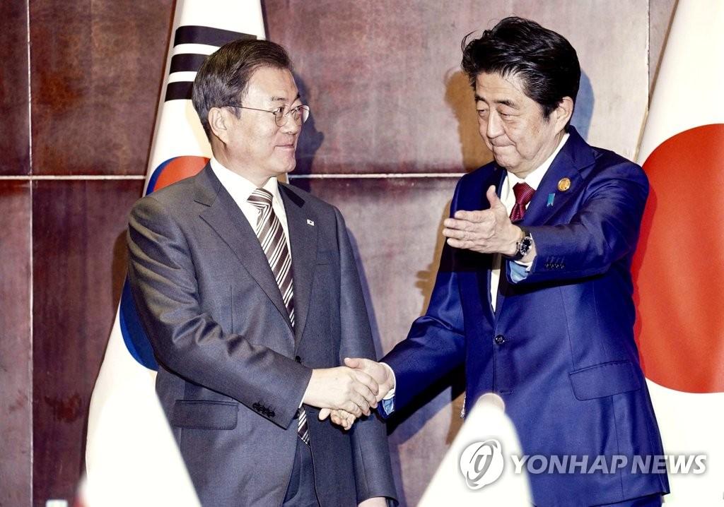 资料图片:12月24日,在成都,韩国总统文在寅(左)和日本首相安倍晋三握手合影。 韩联社