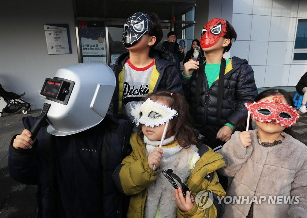 小朋友们带面具观看2019年最后一场日偏食。 韩联社