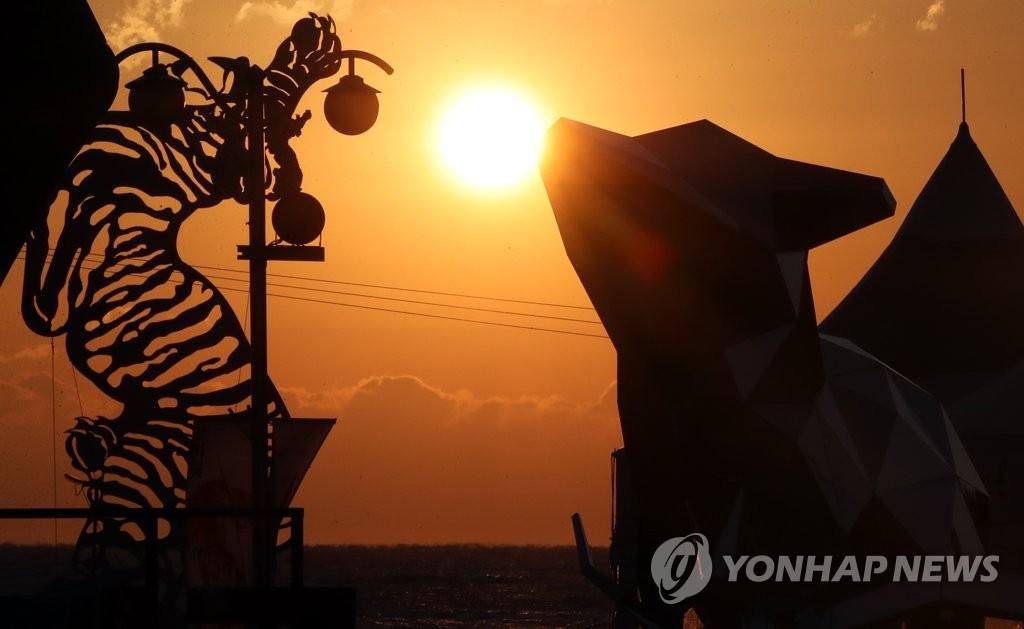 资料图片:12月31日,庆尚北道浦项市虎尾岬的日出景观唯美如画,象征鼠年的雕像增添迎新气氛。虎尾岬是韩国有名的观日出胜地。 韩联社