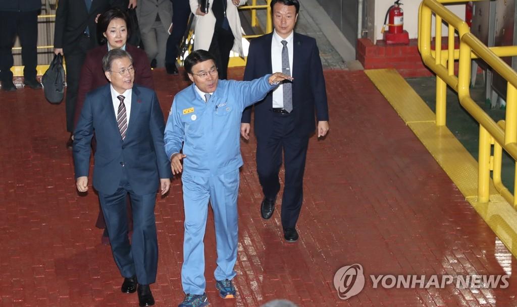 1月9日,在浦项制铁智能工厂,浦项制铁会长崔正友(穿着蓝色衣服)指引文在寅(左)参观。 韩联社