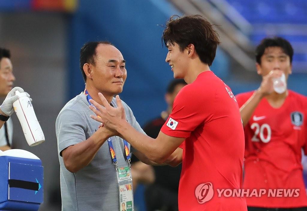 当地时间1月12日下午,在泰国宋卡,韩国队在亚足联U23锦标赛决赛阶段比赛暨2020东京奥运会男足预选赛的第二轮比赛上以2比1战胜伊朗队。图为主帅金鹤范(左)与曹圭成共同庆祝进球。 韩联社