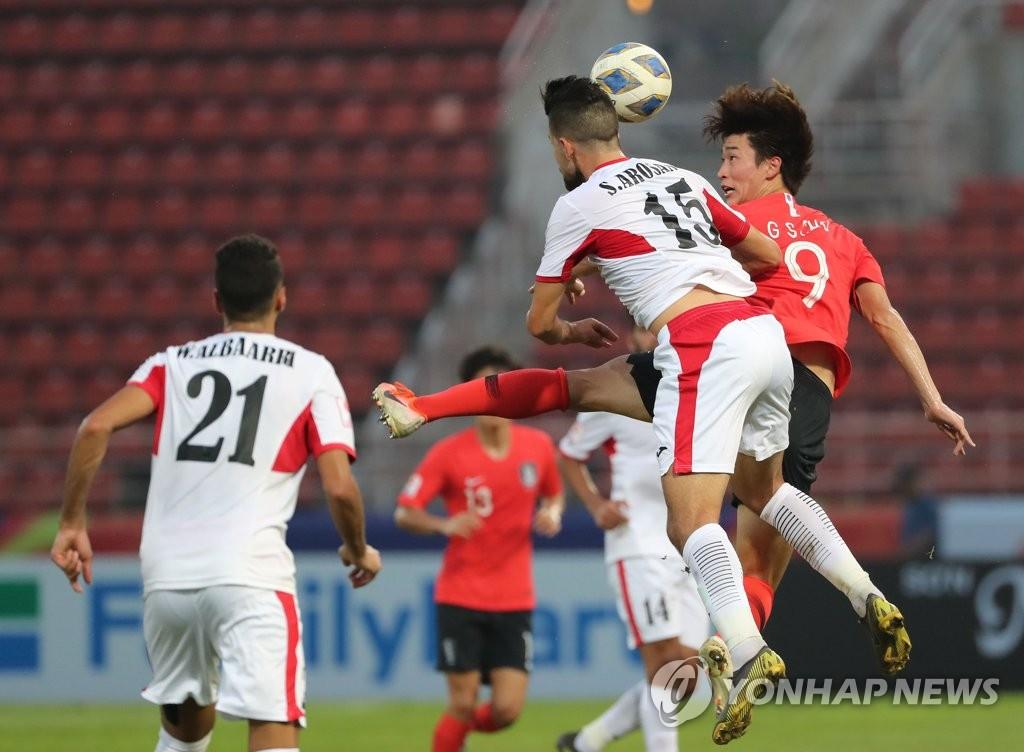 1月19日,在泰国进行的韩国对战约旦的比赛中,韩国队员赵圭成以头抢球。 韩联社