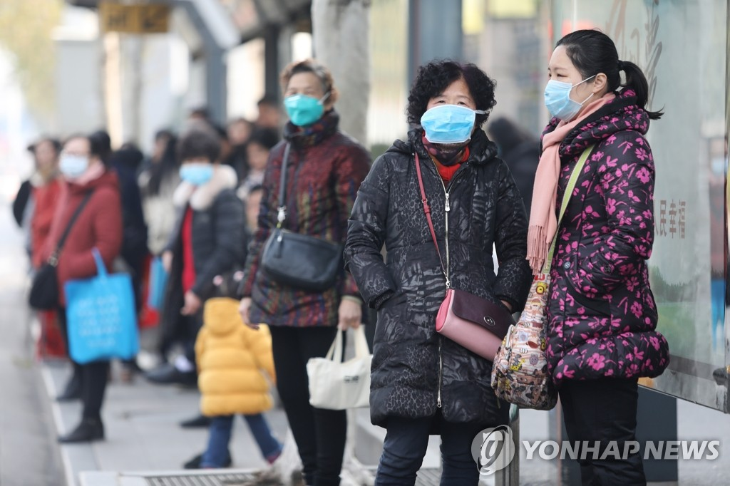 资料图片:1月20日,在中国武汉,市民们戴着口罩出行。近期,武汉市发生新型冠状病毒肺炎。 韩联社/欧新社 (图片严禁转载复制)