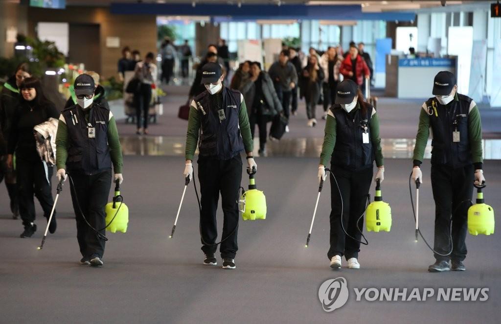 1月21日上午,在仁川国际机场第一航站楼国际到达大厅,工作人员正在消毒防范新型冠状病毒肺炎疫情流入。 韩联社