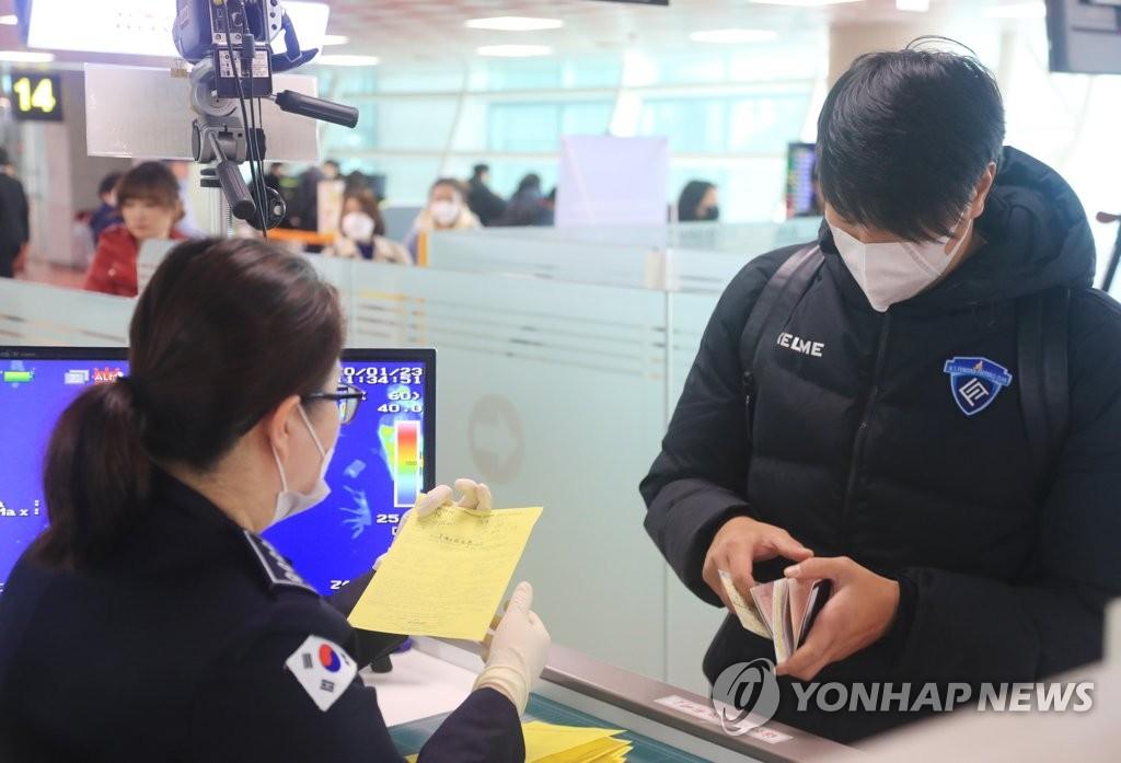 资料图片:1月23日上午,在济州机场,韩国疾控部门职员使用红外测温仪筛查发热旅客并确认中国入境者的健康状态问卷。 韩联社