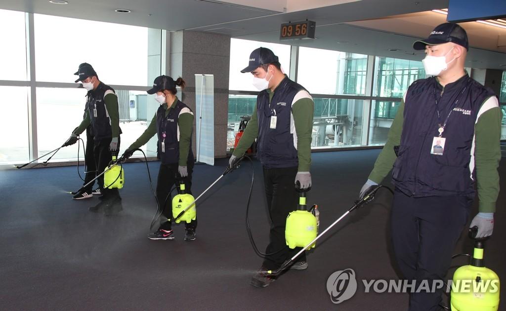 资料图片:1月24日上午,在仁川国际机场到达大厅,工作人员正在消毒防范新型冠状病毒肺炎疫情流入。当天,韩国出现第二例新型冠状病毒感染的肺炎病例。 韩联社