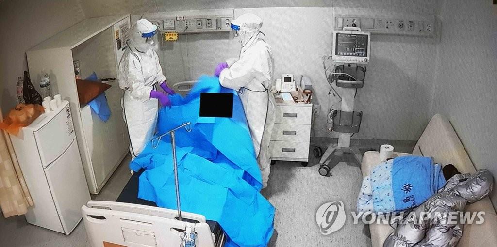 资料图片:1月27日,在京畿道明知医院,医护人员对确诊患者进行治疗。 韩联社/明知医院供图(图片严禁转载复制)