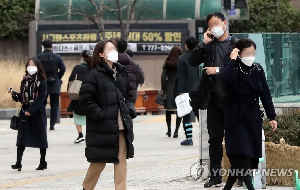 资料图片:1月28日,在首尔光化门,多名市民戴着口罩上班。 韩联社