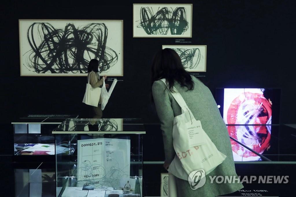 """资料图片:1月28日下午,韩国男团防弹少年团(BTS)携手现代美术巨匠进行的美术展示活动""""CONNECT,BTS""""在首尔东大门设计广场开幕,一名访客前来观看展览。 韩联社"""