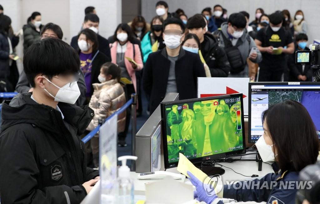 资料图片:1月28日,在釜山金海机场到达厅,来自中国的游客接受体温检测。 韩联社