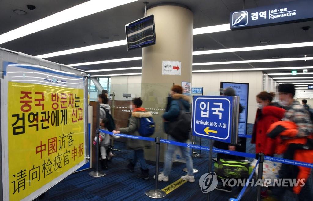 资料图片:1月28日,在釜山金海机场,中国旅客接受入境审查。 韩联社