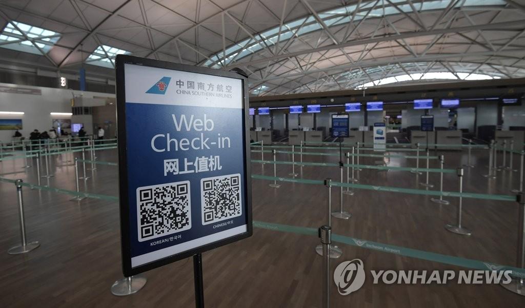 资料图片:1月29日,在仁川国际机场,办理中国航线值机手续的柜台前十分冷清。 韩联社
