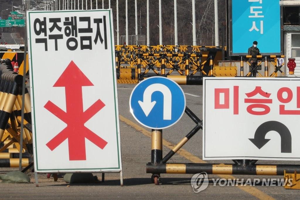 资料图片:1月30日,在京畿道坡州市统一大桥,一名哨兵戴着口罩站岗。 韩联社