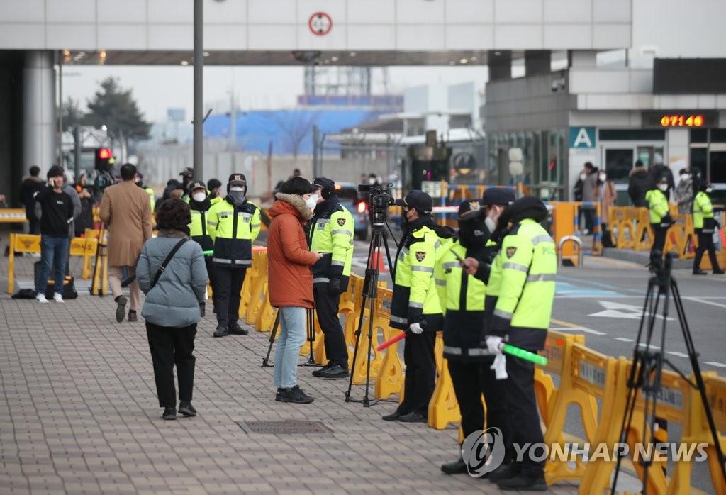 1月31日上午,在金浦机场,韩国警察临时围护转移疫区公民的道路。 韩联社