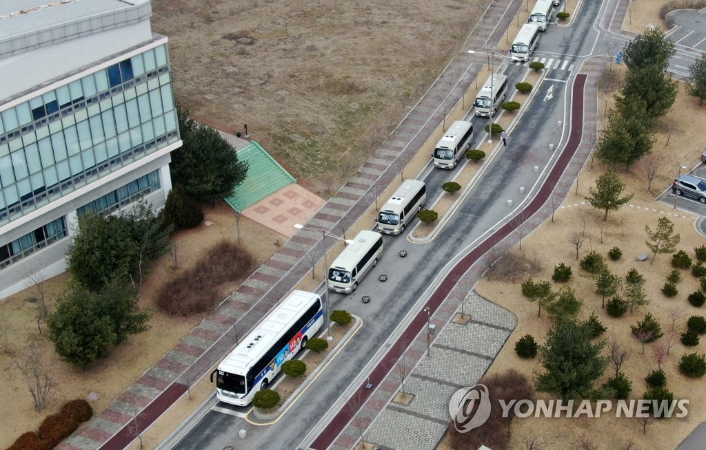 1月31日,乘坐政府包机从武汉回国的人员乘坐车辆驶入位于忠清南道牙山市的警察人才开发院。 韩联社