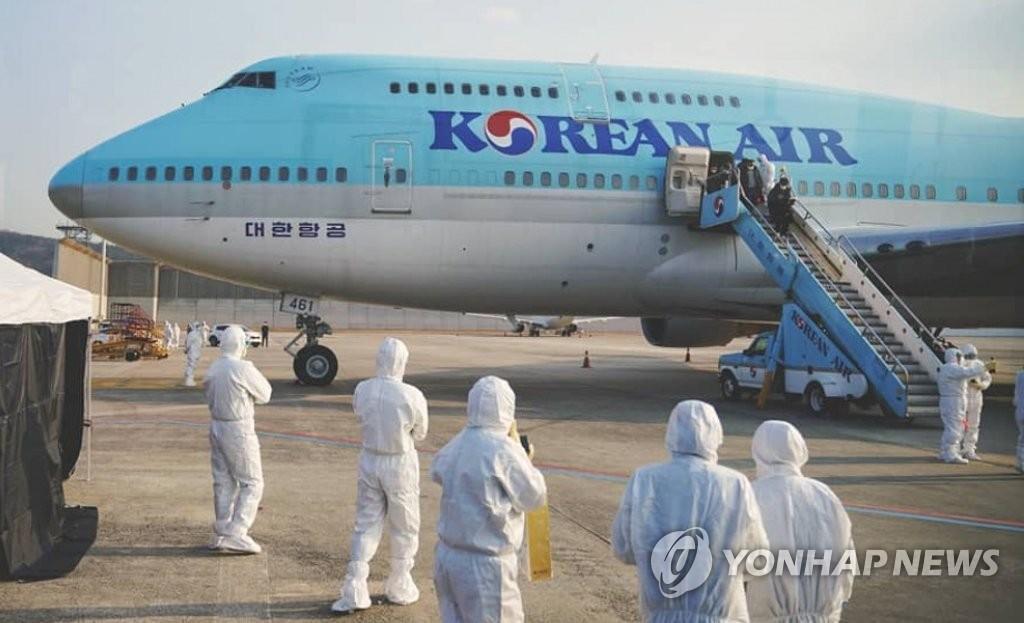 1月31日上午,在金浦机场,乘坐政府派遣的包机从武汉回国的韩国侨胞下机。 韩联社/读者供图(图片严禁转载复制)