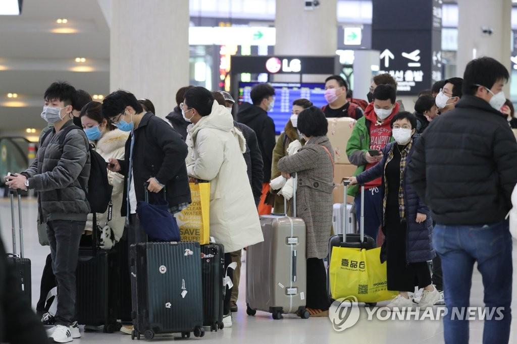 2月3日,在济州国际机场,旅客排队办理登机手续准备飞赴中国上海。 韩联社