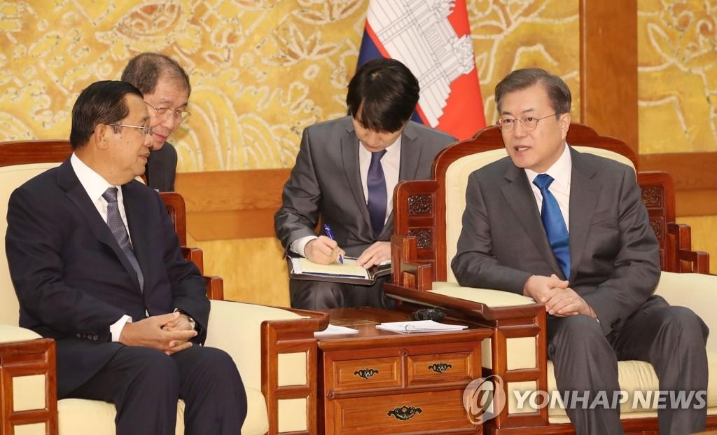 2月4日,在青瓦台,韩国总统文在寅(右)与柬埔寨首相洪森交谈。 韩联社