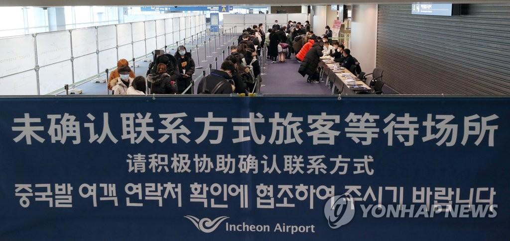 资料图片:2月5日,在仁川国际机场第一航站楼自华旅客专用入境处,工作人员在一一确认旅客在韩联系电话。 韩联社