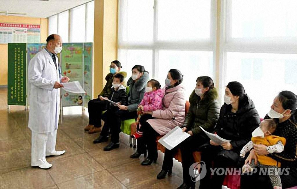 平壤医护人员向居民宣传防范新冠病毒扩散的知识。韩联社/《劳动新闻》官网截图(图片仅限韩国国内使用,严禁转载复制)