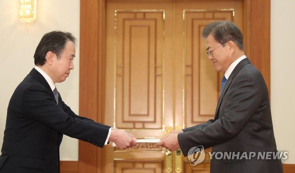 2月7日,在青瓦台,韩国总统文在寅(右)接受日本新任驻韩大使富田浩司递交国书。 韩联社