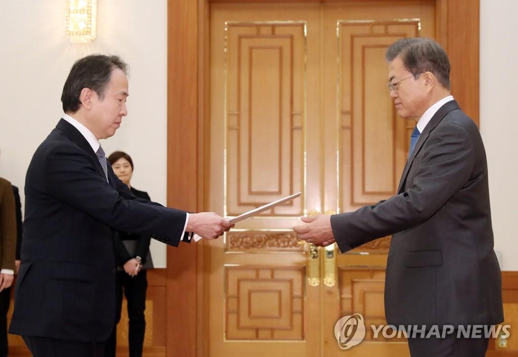 2月7日,在青瓦台,韩国总统文在寅(右)接受日本驻韩大使富田浩司递交的国书。 韩联社