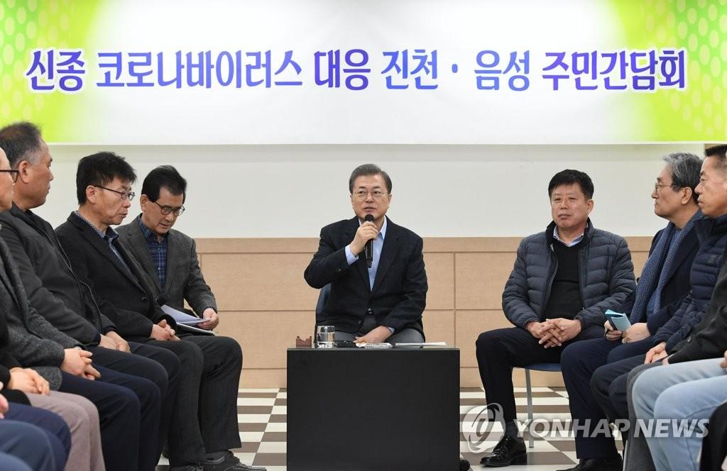 2月9日,文在寅(中)在镇川与当地居民恳谈。 韩联社