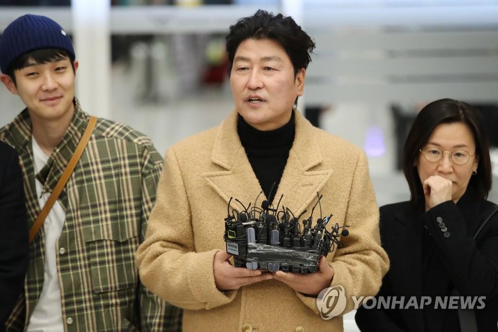2月12日,在仁川国际机场第二航站楼,主演《寄生虫》的宋康昊(右二)接受媒体采访。 韩联社