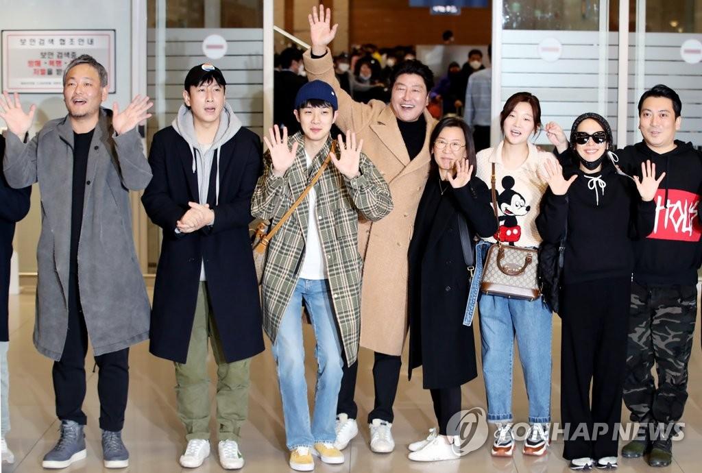 2月12日,在仁川国际机场第二航站楼,在美国洛杉矶出席第92届奥斯卡金像奖颁奖礼后回国的电影《寄生虫》主创人员向媒体记者挥手致意。 韩联社
