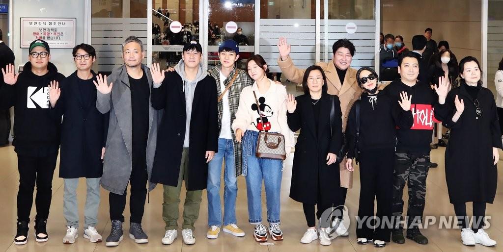 资料图片:2月12日,在仁川国际机场第二航站楼,在美国洛杉矶出席第92届奥斯卡金像奖颁奖礼后回国的电影《寄生虫》主创人员向媒体记者挥手致意。 韩联社