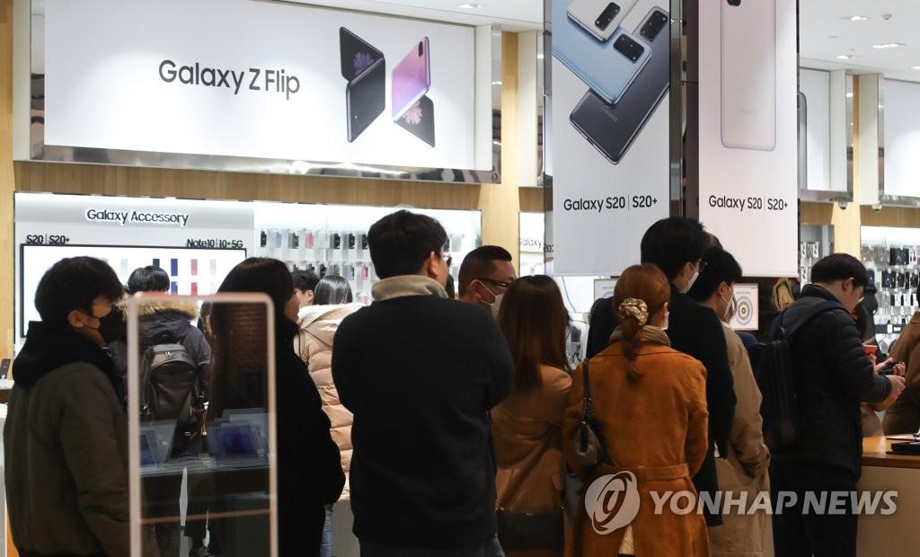 资料图片:2020年2月14日,在位于首尔瑞草区的三星电子专卖场,用户排长队等候体验Galaxy Z Flip。 韩联社