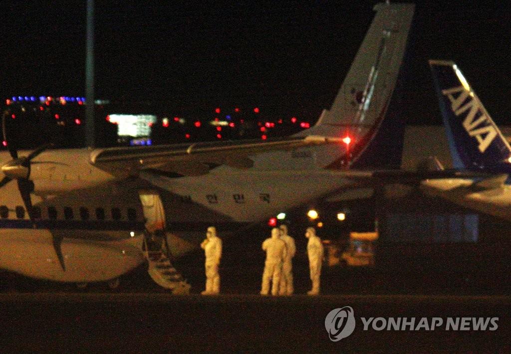 """资料图片:2月19日凌晨,在东京羽田机场,""""钻石公主""""号邮轮上6名韩国公民和1名日本家属正在搭乘韩国总统专机""""空军3""""号机。 韩联社"""