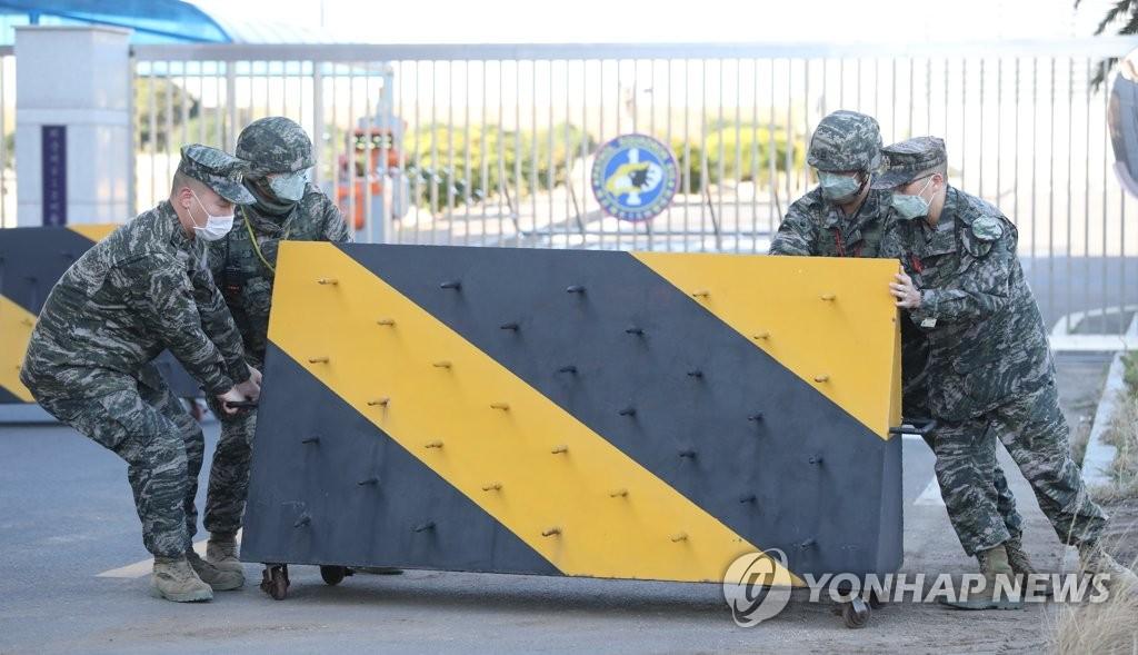 资料图片:2月21日,在济州国际机场内的海军第615飞行大队门前,官兵们在入口处设置街垒防疫。20日,该部队A某士兵确诊感染新冠病毒(COVID-19)。这是韩军部队首现新冠病毒感染者。 韩联社