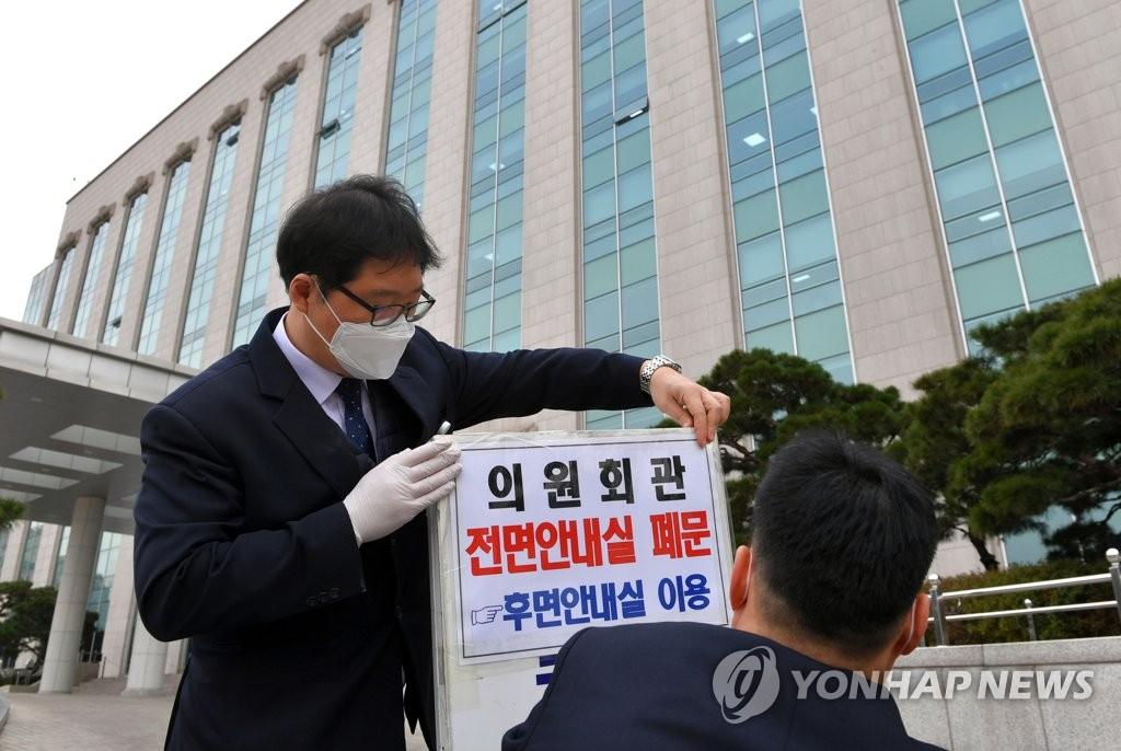 2月24日,在韩国国会,工作人员在门口贴上关于议员会馆关闭的通知。 韩联社