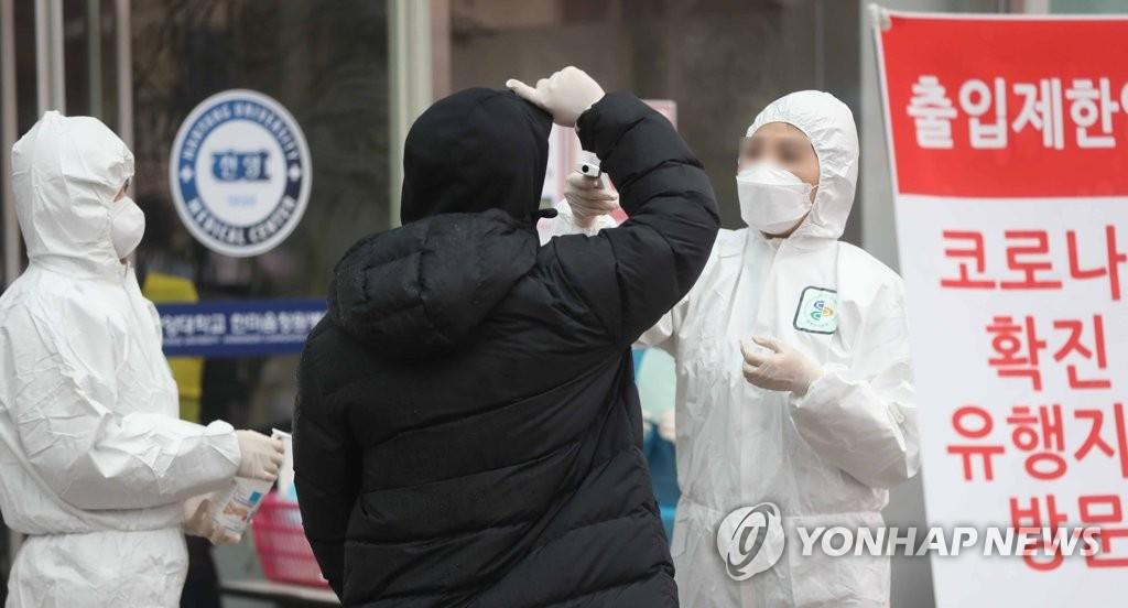 资料图片:2月25日,在庆尚南道昌原市一家医院,防疫人员测量访客体温。 韩联社