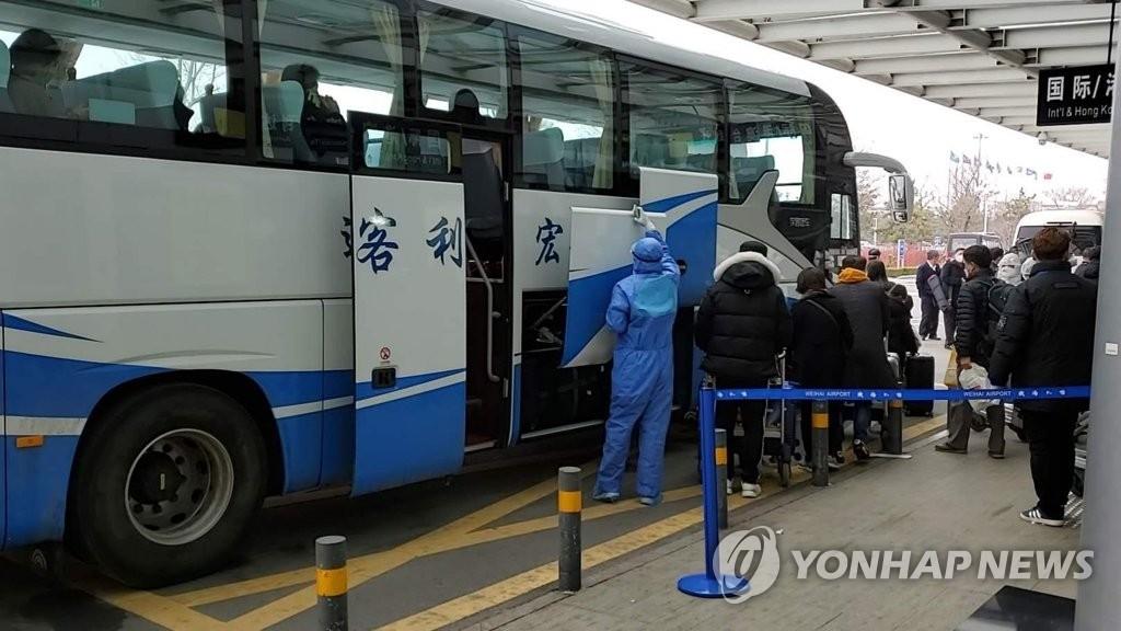 资料图片:2月25日,从韩国仁川飞抵中国威海的济州航空7C8501航班的乘客乘车前往隔离设施。 韩联社/读者供图(图片严禁转载复制)