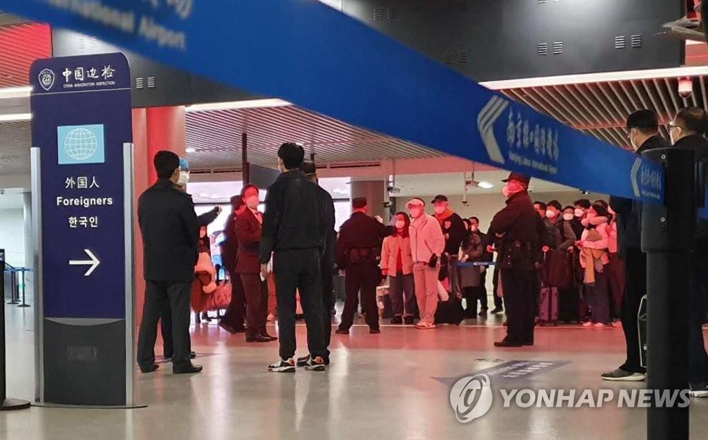 资料图片:2月25日,在南京机场,韩国乘客接受中方工作人员的检疫。 韩联社/读者供图(图片严禁转载复制)