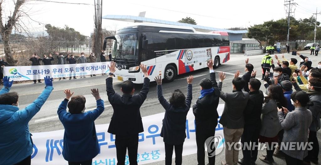 2月27日,在利川市的联合军事大学国防语言学院,当地居民为解除隔离乘车离开的侨民送行。 韩联社