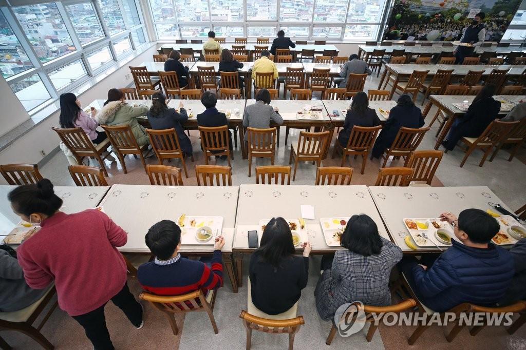 资料图片:2月27日,在大邱市寿城区的大邱市教育厅单位食堂内,员工们坐在餐桌的一侧,避免面对面进餐。韩联社