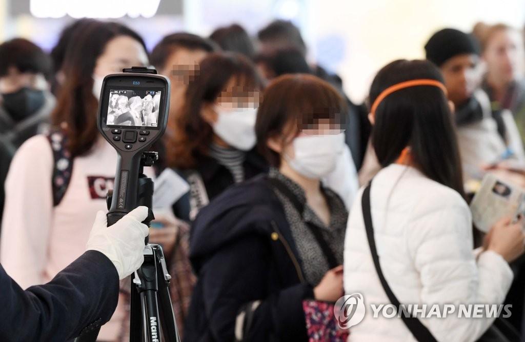 资料图片:2月28日,在仁川国际机场洛杉矶航班登机口,大韩航空工作人员筛查发热旅客。 韩联社