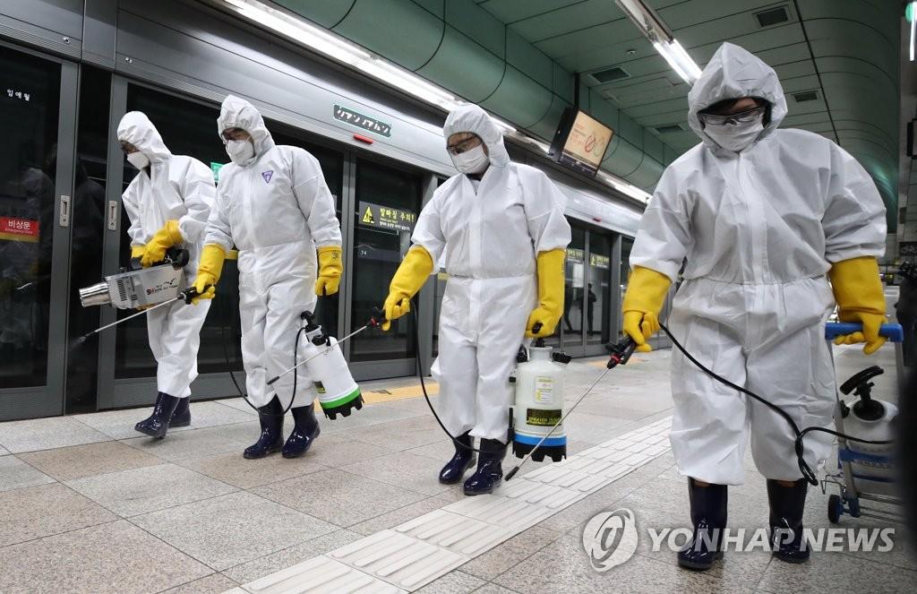 资料图片:2月28日下午,在首尔光化门站,防疫人员在站内喷洒消毒液。 韩联社