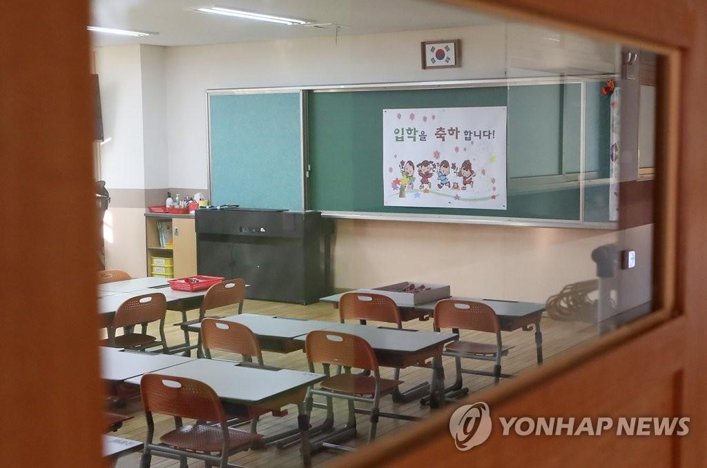 资料图片:3月2日,位于首尔市的一间小学教室空无一人,黑板上只贴着庆祝入学的纸条。随着新型冠状病毒疫情扩散,韩国各级学校推迟开学日期。 韩联社