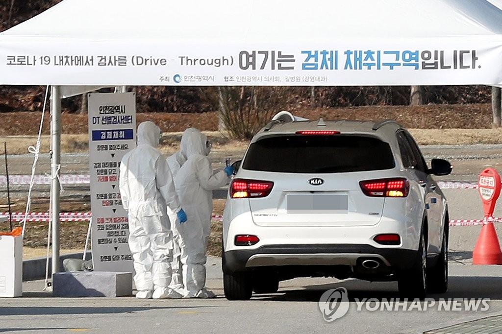 """资料图片:3月2日,在设于仁川市延寿区的""""免下车""""筛查诊所,一名市民在车内接受新冠病毒(COVID-19)检测。 韩联社"""