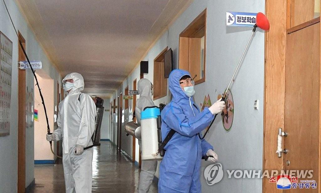 """资料图片:3月3日,在朝鲜一学校,防疫人员进行防疫消毒。 韩联社/朝鲜外宣媒体""""朝鲜的今天""""官网画面截图(图片严禁转载复制)"""