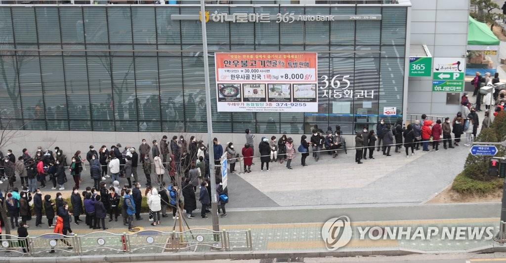 3月3日,在首尔市麻浦区道的一处口罩指定销售点,人们排长龙等待购买。 韩联社
