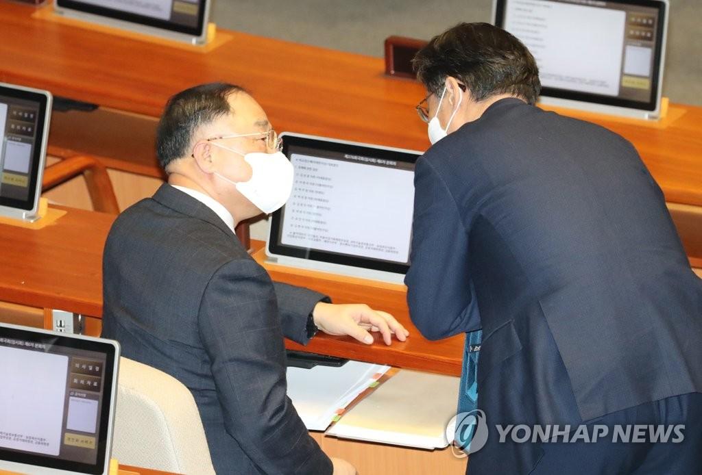 3月3日,在国会,副总理兼企划财政部长官洪楠基(左)出席国会质询政府工作会议。 韩联社