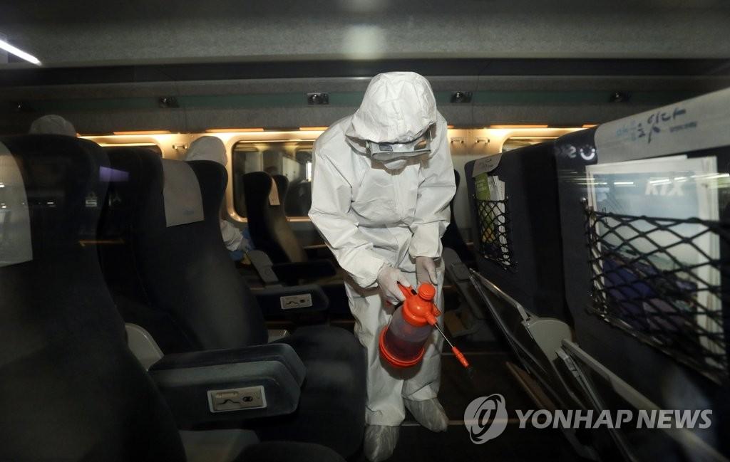 资料图片:防疫人员对列车内部进行消毒。 韩联社