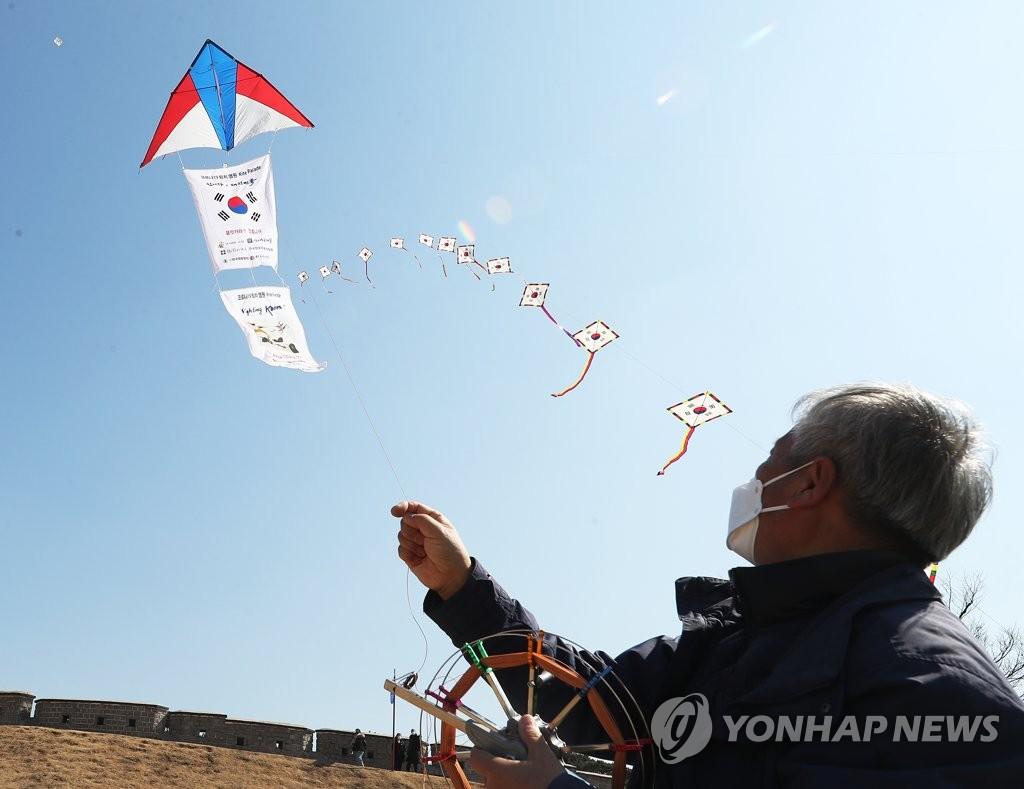资料图片:3月5日,在京畿道水原市世界文化遗产华城的苍龙门前,韩国风筝联盟水原分会会员们放风筝,祈愿新型冠状病毒疫情早日平息。 韩联社