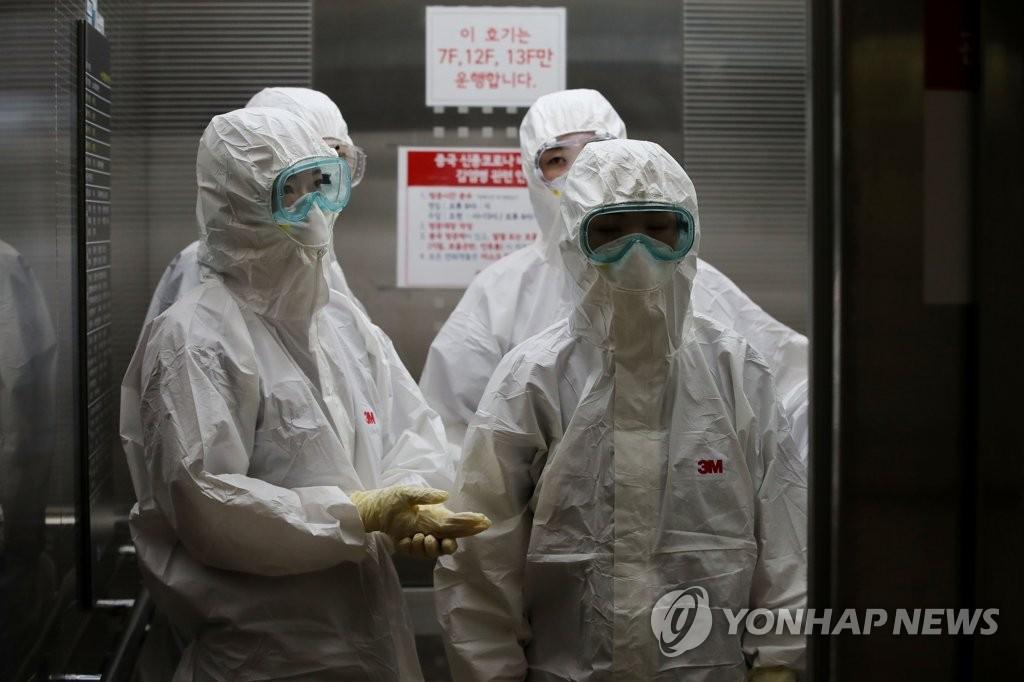 资料图片:3月9日,在新冠病例定点收治医院首尔医疗院,全副武装的医护人员乘电梯前往负压病房。韩联社